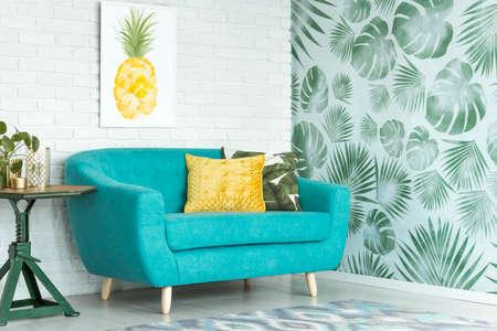 Oreiller jaune sur un canapé turquoise contre le mur de briques avec affiche ananas au salon avec des feuilles de papier peint Banque d'images - 91911660