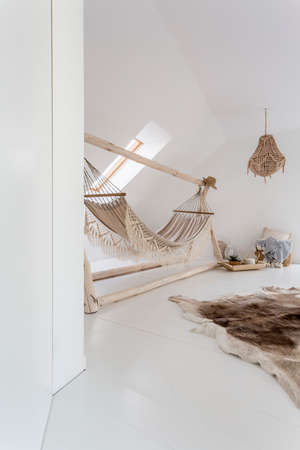 White room with handmade lampshade and hammock in the attic