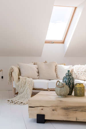 Gold lantern on wooden table in living room on attic with beige knit blanket and pillows on sofa
