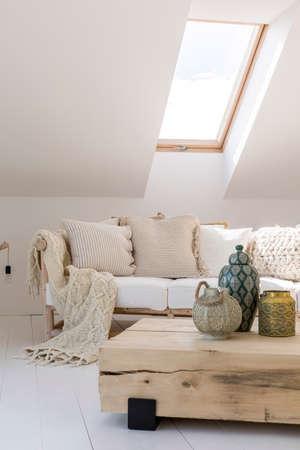 Linterna de oro en la mesa de madera en la sala de estar en el ático con manta de punto beige y almohadas en el sofá Foto de archivo - 92683633