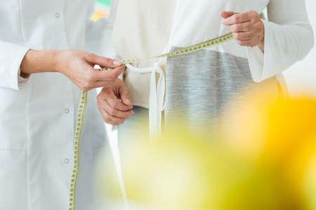 女性患者と体の周囲を測定する栄養士のクローズアップ 写真素材