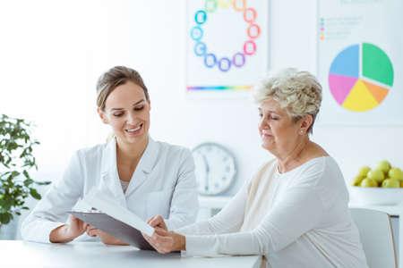 Lächelnder Ernährungswissenschaftler, der ihrem älteren Patienten personalisierten Gewichtverlustdiätplan zeigt Standard-Bild