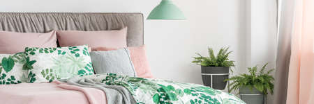 Pastel bed with headboard, decorative cushions and botanic patterned bedding next to window Stock Photo