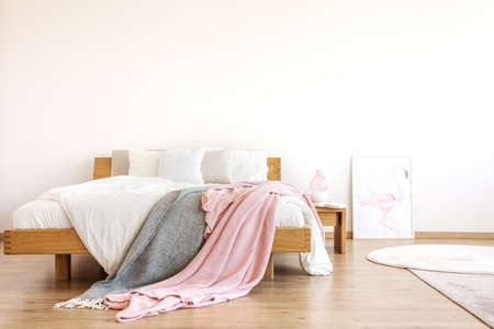 Grey and pastel pink blankets thrown on wooden bed with white bedding