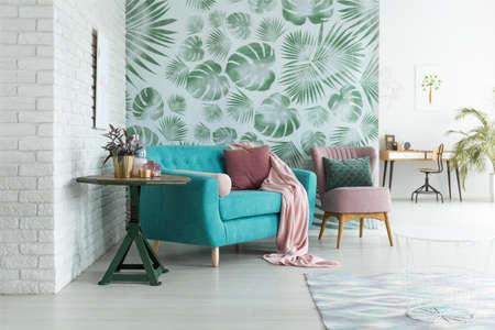 Grüner Tisch mit Pflanze neben blauem Sofa und rosa Sessel mit Kissen gegen grüne Tapete im Wohnzimmer