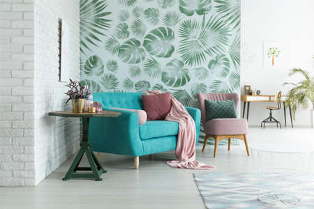 Green table with plant next to blue sofa and pink armchair with pillow against green wallpaper in living room