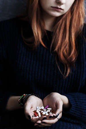 Close-up of teenagers hands with drugs. Drug addiction of young person concept