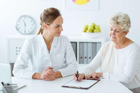 Patiënt met diabetes die dagelijkse eetgewoonten schrijft tijdens een vergadering met diëtist Stockfoto