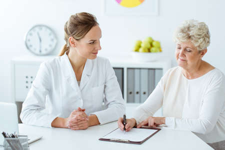 Patient with diabetes writing daily eating habits during a meeting with dietician Stock Photo