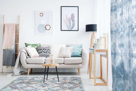 파란색 커튼, 포스터와 베개와 소파 옆에 사다리에 담요와 거실에서 카펫