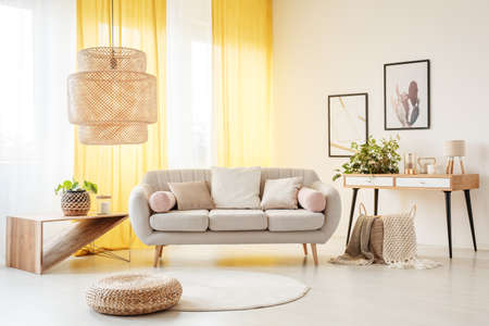 Lámpara de ratán sobre el puf y la alfombra en la sala de estar bohemia con sofá, plantas y cortinas amarillas