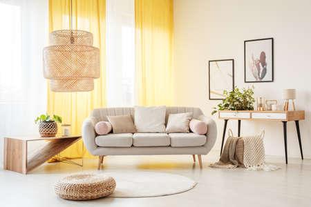 Rattanowa lampa nad pufą i dywanem w artystycznym salonie z kanapą, roślinami i żółtymi zasłonami