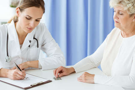 Professional doctor with stethoscope writing prescription for dietary supplements to a patient