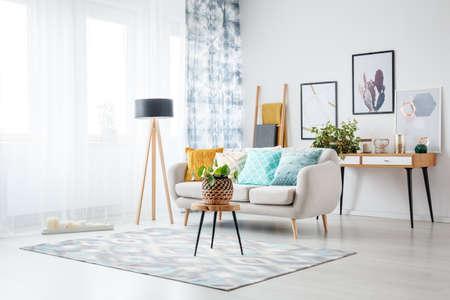 Banquinho com planta no tapete e lâmpada na sala de estar com cartazes acima do armário atrás do sofá com almofada azul