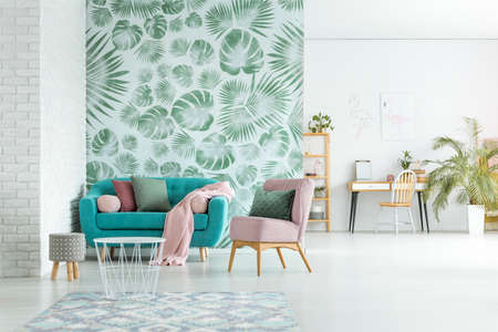 Pink armchair and blue settee with blanket in bright living room with stool and white table against leaves wallpaper
