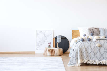 White bedroom with two posters placed by the bed with bright coverlet and cotton balls Archivio Fotografico
