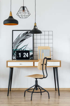 Simple and natural start-up office interior with laptop on wooden desk, chair and organizer