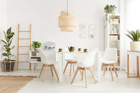 Big wicker lampshade hanging above table in white dining room interior with potted plants and plastic chairs Stock Photo
