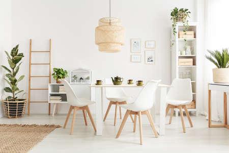 Grote rieten lampenkap opknoping boven tafel in witte eetkamer interieur met potplanten en plastic stoelen
