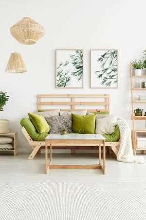 Posters with plants hanging on white wall in stylish living room interior with green lounge and wooden table