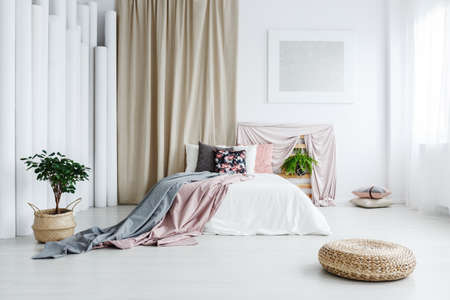 Round wicker footrest on the floor in feminine bedroom with curtain and silver painting