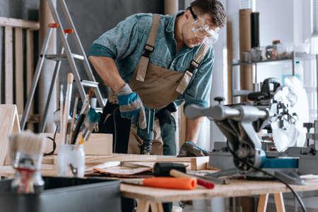 Jonge aannemer die een gat in een stuk hout in zijn workshop boort