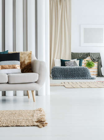 Bed with grey knit blanket and pillows in a bright interior with couch in the foreground Stock Photo