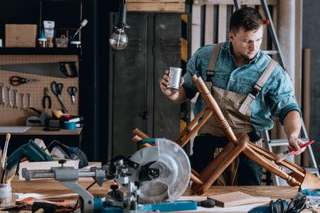 Geconcentreerde timmerman die de vernieuwing van een vintage houten stoel beëindigt