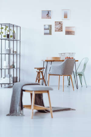 Grey blanket on bench in bright dining room with chair at table against wall with gallery