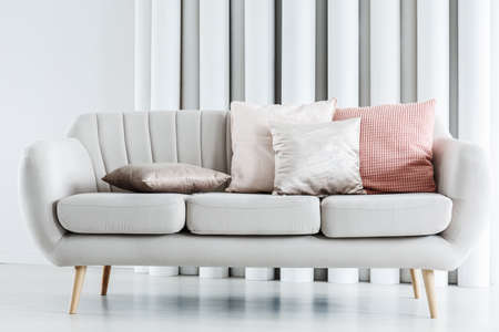 Close-up photo of bright grey couch with silver and pink cushions