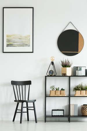 Sedia e mensola nere classiche con le piante contro la parete bianca con la pittura e lo specchio rotondo nella stanza luminosa Archivio Fotografico - 97990603