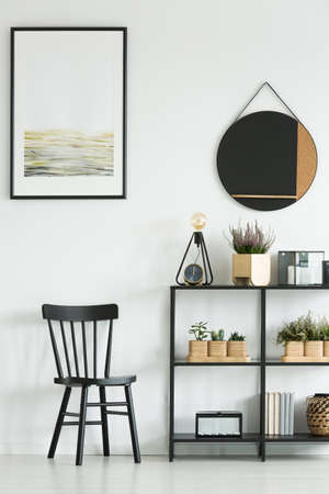 Classic black chair and shelf with plants against white wall with painting and round mirror in bright room Foto de archivo