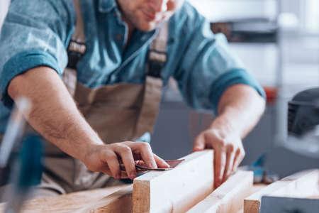 Close-up van mannelijke timmerman die schuurpapier op een stuk hout voor meubilair gebruiken Stockfoto