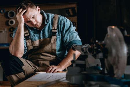 Ongerust gemaakte zakenman die een moeilijk productieprobleem in zijn workshop behandelen Stockfoto
