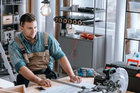 Glimlachende arbeider trots van zijn het planzitting van de huisvernieuwing bij een houten bureau in zijn workshop