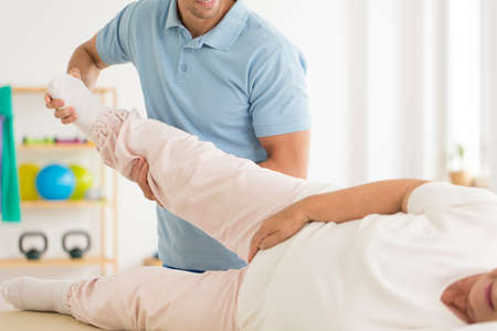 Close-up of personal physiotherapist rehabilitating senior woman's joints after hip reconstruction Stockfoto