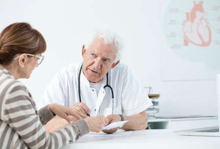 Elderly cardiologist consulting tests results with the patient after the infarction