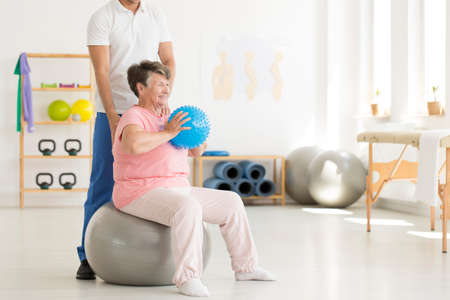 Happy senior woman sitting on grey ball and holding blue ball while exercising at gym Stock Photo