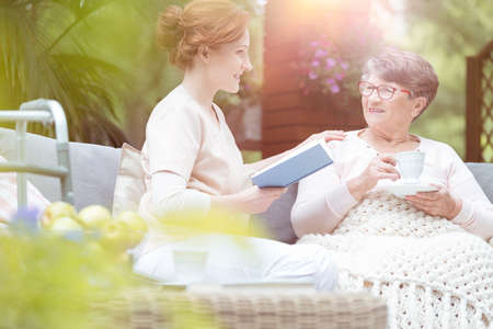 Old woman talking to a young caregiver reading a book during meeting on a terrace