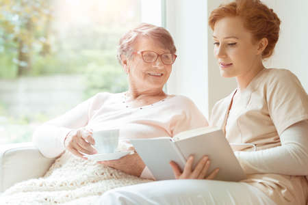 Woman reading a book while sitting with happy grandmother drinking tea