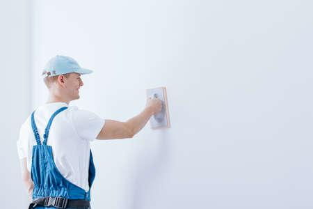 Mannelijke stukadoor in workwear holdingsspatel en het voorbereiden van ruwe muur voor het schilderen