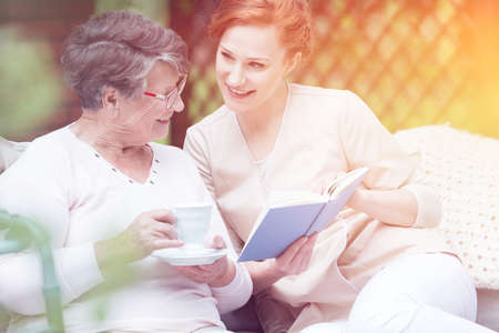 Caregiver reading a book and spending time with an elderly woman on a terrace