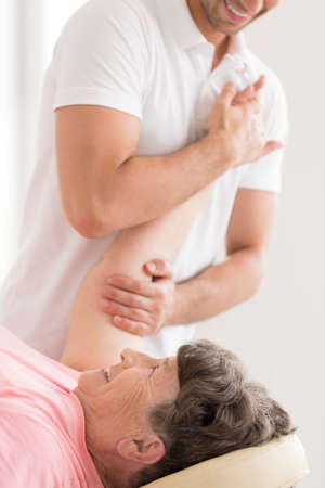 Professional physiotherapist stretching senior womans shoulder during pain treatment