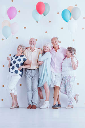Group of enthusiastic senior friends with colorful balloons celebrating birthday