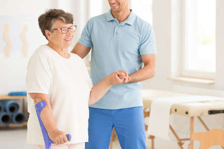 Uśmiechnięty fizjoterapeuta wspierający niepełnosprawną starszą kobietę po kontuzji
