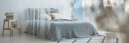 Wooden table in classic bedroom interior with grey blanket and pillows on bed behind veil Banco de Imagens