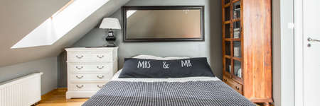 Simple bedroom for married couple with big mirror hanging on the wall above king-size bed Stock Photo