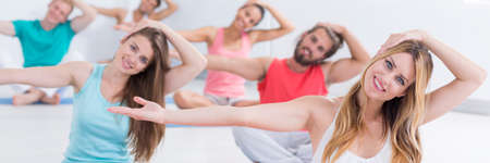 Smiling and relaxed participants of yoga classes stretch the neck muscles
