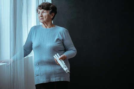黒い背景に折り畳まれた白いサトウインドウを持つ窓の隣の盲目の高齢女性のコピースペース