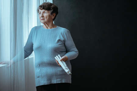 Copy space of blind elderly woman next to a window with folded white cane against black background